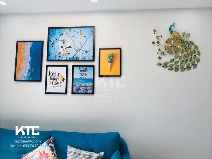Mảng tường phòng khách nổi bật với mảng tranh theo phong cách trẻ trung hiện đại. Đồng hồ chim công cách điệu sáng cả căn phòng